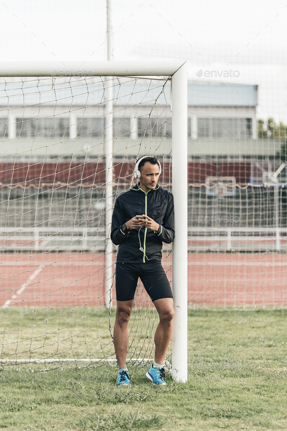 Athlete leaned on the goalpost, listening to music - Stock Photo - Images