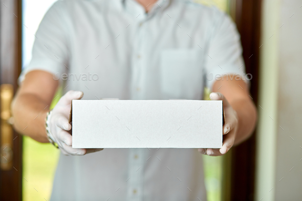Courier, delivery man in medical latex gloves and mask safely - Stock Photo - Images