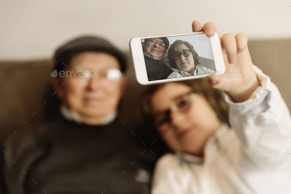Grandfather and grandson are taking selfie. - Stock Photo - Images
