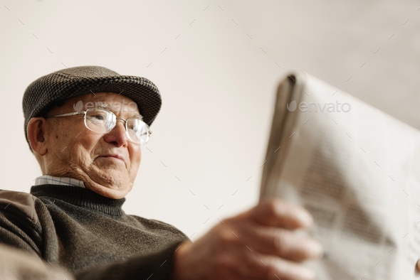 Elderly man reading a newspaper. - Stock Photo - Images