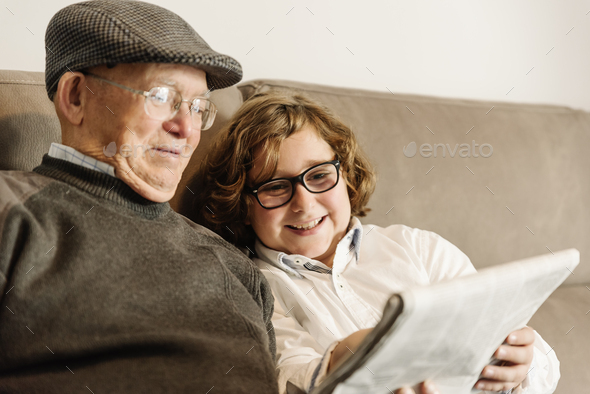 Grandfather and grandson reading the news. - Stock Photo - Images