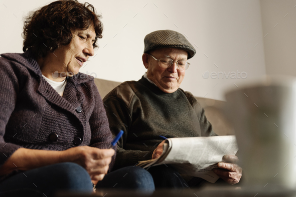 Elderly couple reading a newspaper. - Stock Photo - Images