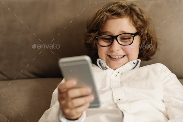 Child boy using his mobile phone. - Stock Photo - Images
