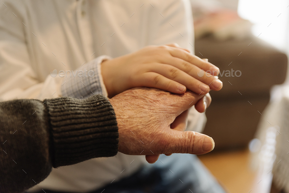 Hand of old person holding hand of kid. - Stock Photo - Images