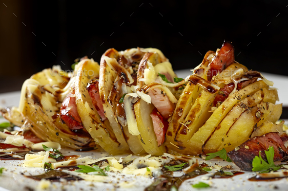 Accordion potatoes filled with bacon, sausages and cheese - Stock Photo - Images