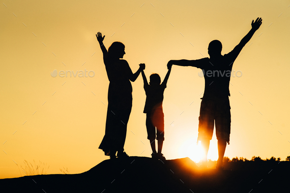 silhouettes of a happy young happy family against an orange sunset - Stock Photo - Images
