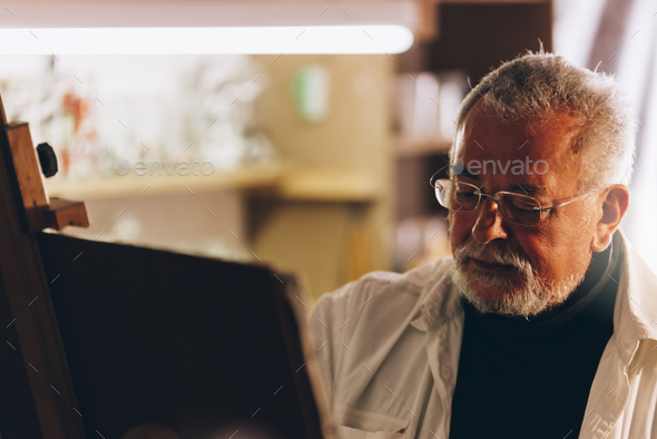 Old man artist painting oils in his studio. - Stock Photo - Images
