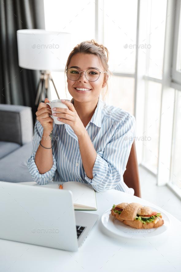 Image of joyful woman drinking coffee and using laptop while sitting - Stock Photo - Images