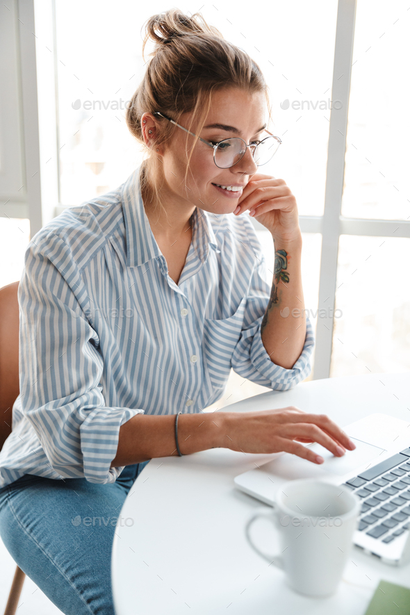 Smiling young businesswoman working on laptop computer - Stock Photo - Images