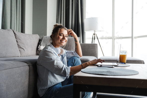 Image of smiling nice woman using laptop while sitting on floor - Stock Photo - Images