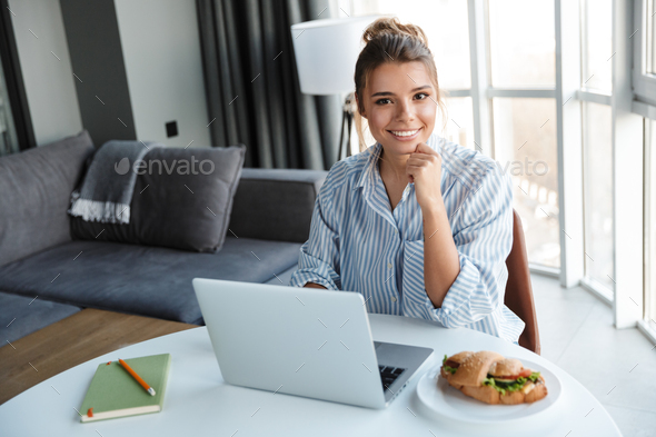 Image of joyful woman smiling and using laptop while sitting at table - Stock Photo - Images