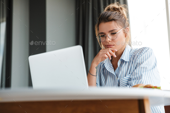 Image of serious nice woman working with laptop while sitting at table - Stock Photo - Images