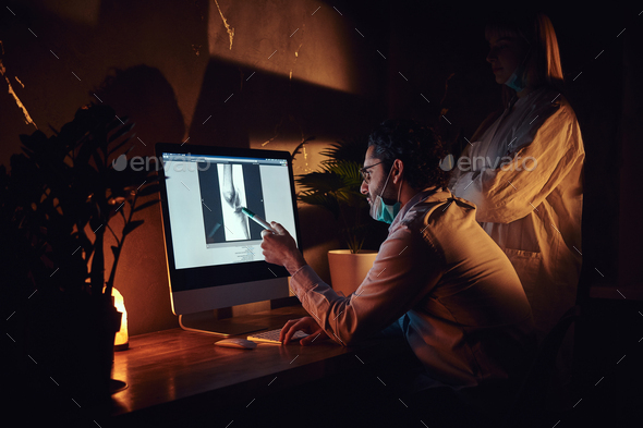 Two docters are working in the dark office - Stock Photo - Images