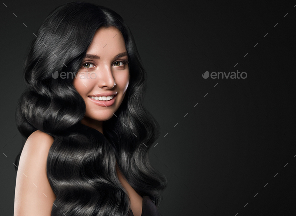 Black hair woman long curly beauty cosmetic concept over black background - Stock Photo - Images