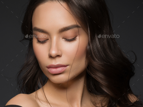 Asian beauty female black background curly black hair natural make up - Stock Photo - Images