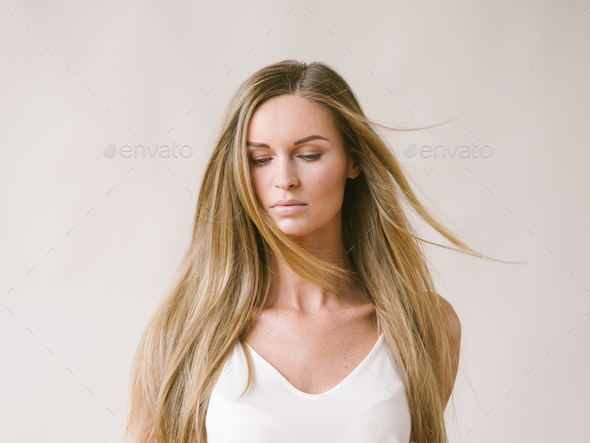 Beautiful woman natural portrait girl with long blonde hair over white gray wall - Stock Photo - Images