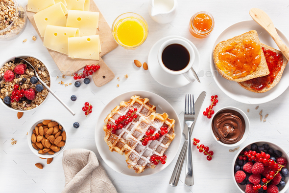 breakfast with granola berry nuts, waffle, toast, jam, chocolate spread and coffee. Top view - Stock Photo - Images
