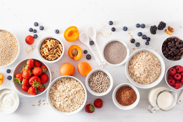 fruits for breakfast. Oatmeal flakes and steel cut, barley, walnut, chia, apricot, strawberry - Stock Photo - Images