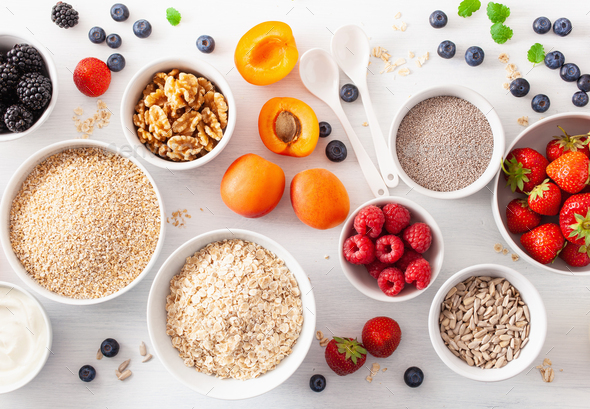 raw cereals, fruits and nuts for breakfast. Oatmeal flakes and steel cut, barley, walnut, chia - Stock Photo - Images