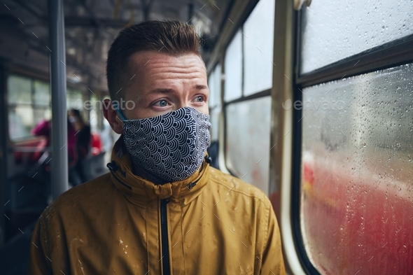 Man wearing face mask in public transportation - Stock Photo - Images