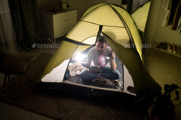 Reading book with flashlight in tent - Stock Photo - Images