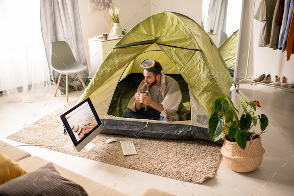 Man drinking tea in tent at home - Stock Photo - Images