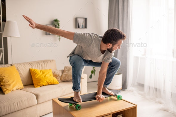 Carefree man skateboarding on coffee table - Stock Photo - Images