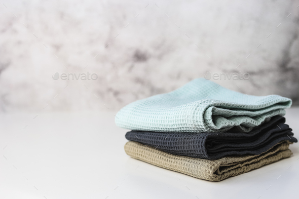 Stack kitchen cotton towels on gray background - Stock Photo - Images