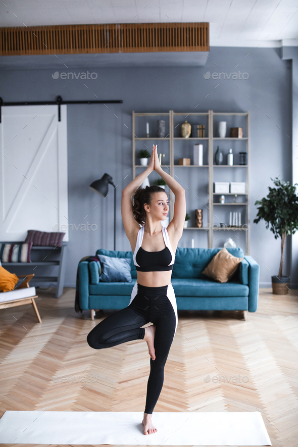 Young beautiful woman practicing yoga, tree pose in living room at home. - Stock Photo - Images