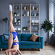 Beautiful woman with a good figure stretching at home in sportswear. - PhotoDune Item for Sale