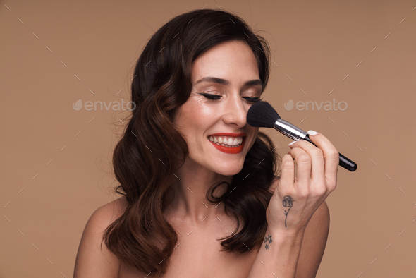 Beauty portrait of adult woman applying cosmetics with makeup brush - Stock Photo - Images
