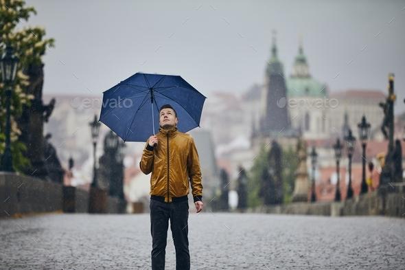 Man with umbrella in heavy rain - Stock Photo - Images