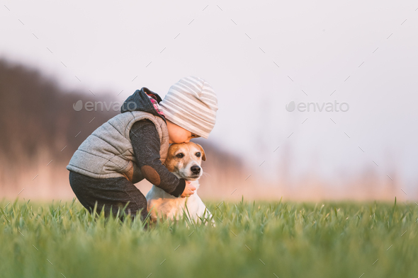 Small kid in yellow jacket with jack russel terrier puppy - Stock Photo - Images