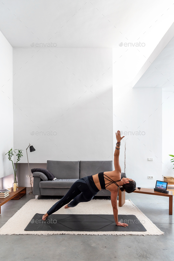 Fit Woman practicing yoga on her mat using an online training program in her tablet - Stock Photo - Images