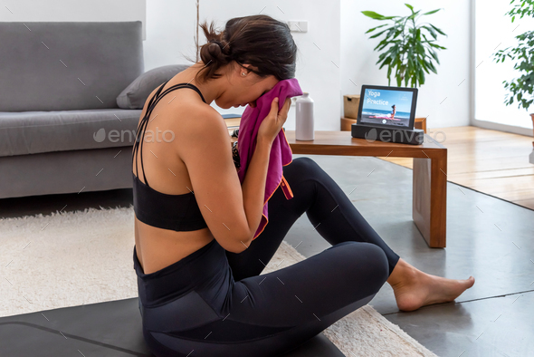 Woman wiping her sweat after practicing an online yoga session at home - Stock Photo - Images
