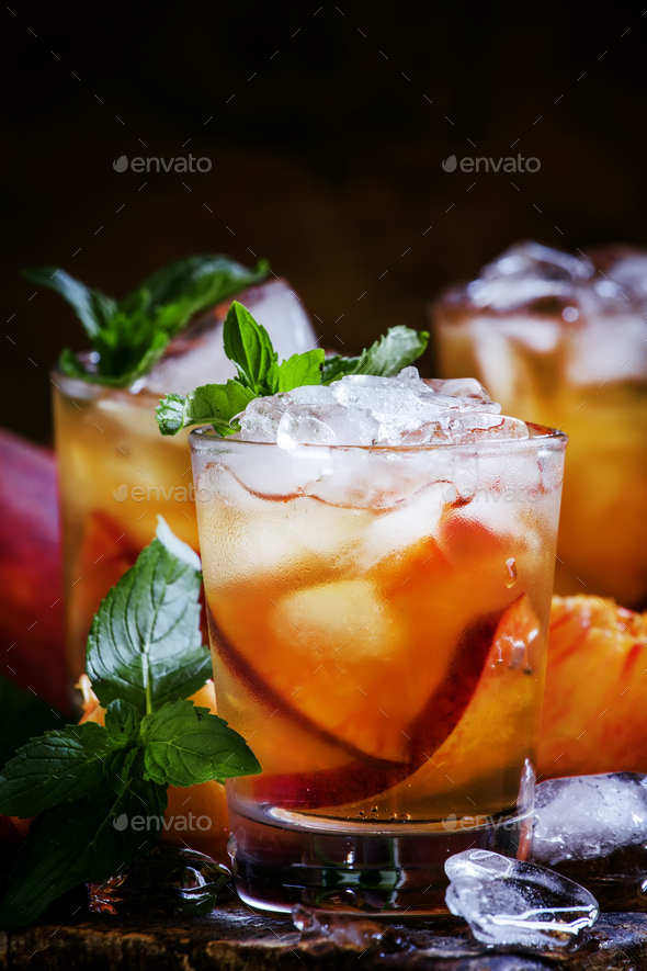 Cold black tea with peach juice, mint and crushed ice - Stock Photo - Images