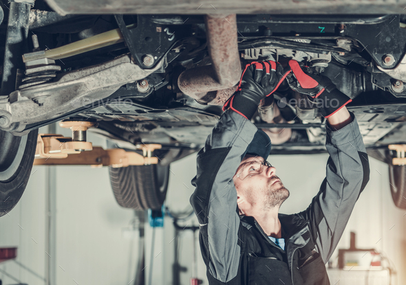 Mechanic Fixing Car Hoisted Up On Hydraulic Lift. - Stock Photo - Images