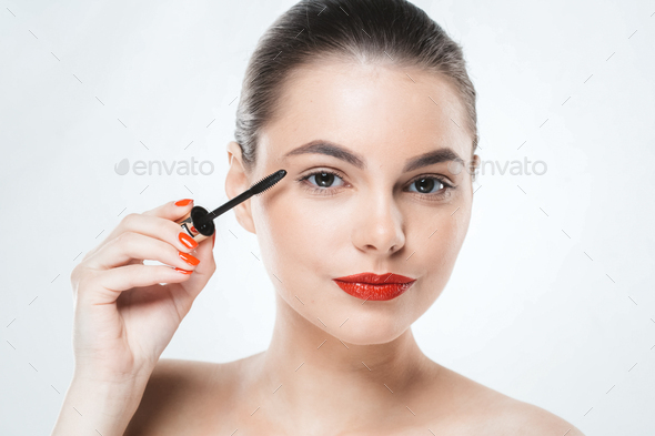 Mascara makeup woman face with red lips and manicure nails isolated on white - Stock Photo - Images