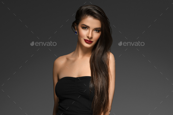 Beautiful woman with long brunette smooth beauty hair over dark backgroun. Female model portrait - Stock Photo - Images