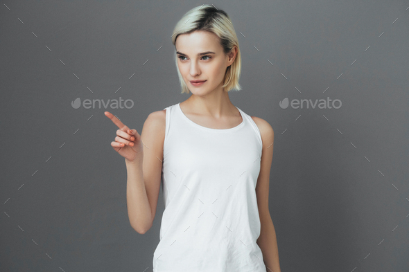 Happy woman pointing finger over gray background - Stock Photo - Images