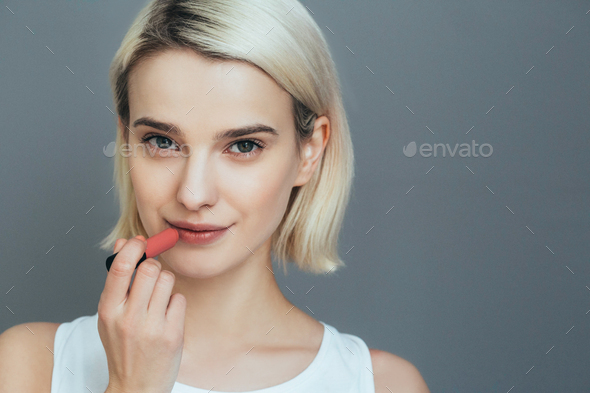 Woman lipstick makeup portrait. Beautiful female with red pink lips over gray wall - Stock Photo - Images