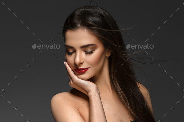 Beautiful woman with long brunette smooth beauty hair over dark backgroun. Female model. - Stock Photo - Images