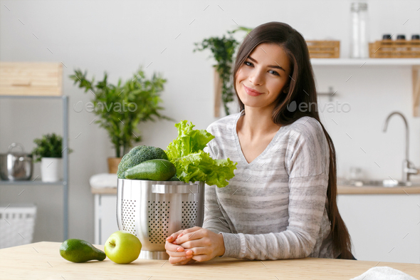 Woman on kitchen home with green vegetables cooking. Helthy home food diet vitamins. - Stock Photo - Images