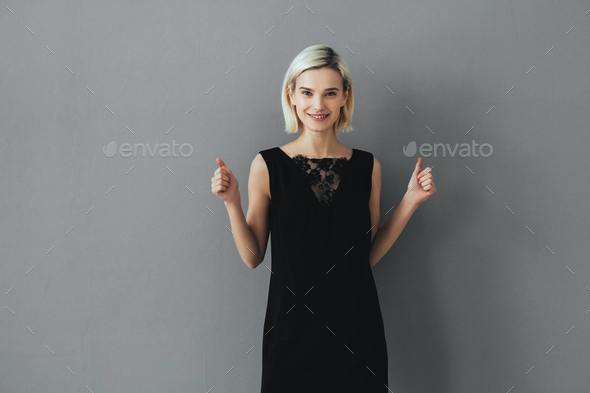 Wooman thumbs up success happy female portrait over gray background - Stock Photo - Images