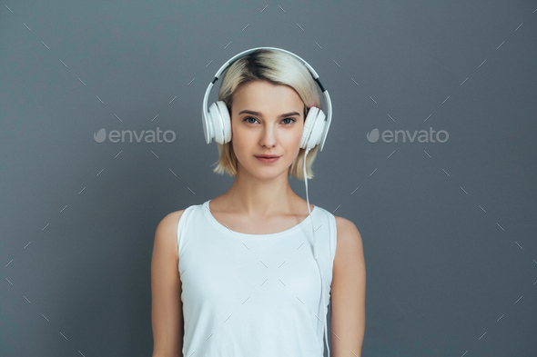 Cute girl in headphones over gray wall - Stock Photo - Images