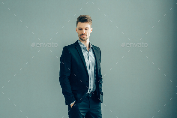 Handsome man in suitover gray wall. Businessman male portrait fashion style guy - Stock Photo - Images