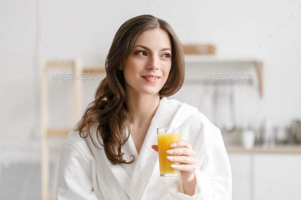 Woman in morning with fresh orange juice in hand. A female in white bathrobe drinking orange juice - Stock Photo - Images