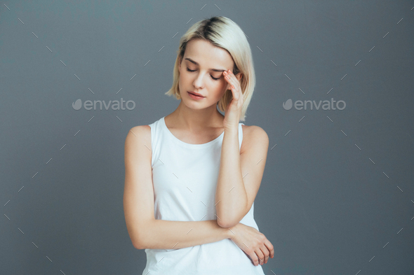 Headache woman portrait. Girl with pain head and neck  over gray wall - Stock Photo - Images