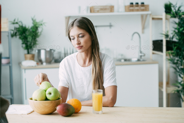 Woman on kitchen with fruits and other food, healthy lifestyle, female home alone - Stock Photo - Images