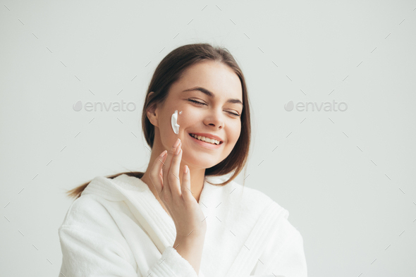 Face cream woman applying crean on skin natural portrait - Stock Photo - Images